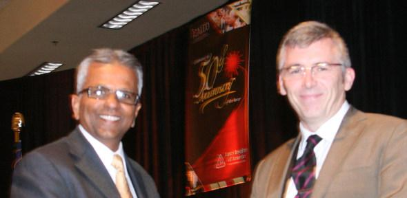 Dr O'Neill (right) receiving his award from the President Dr Raj Patel