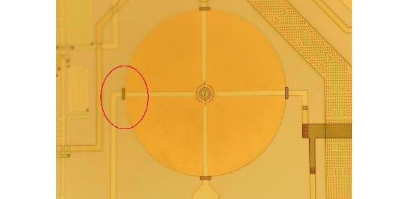 Photograph showing an SOI microhotplate (large circle) with a small micro-heater (12 micron radius)