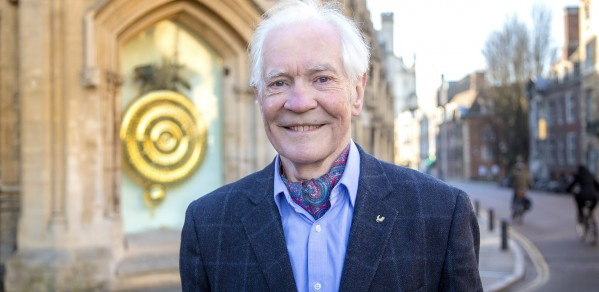 Dr John C Taylor in front of the popular Corpus Chronophage Clock, that he created and donated to his former college