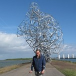 Antony Gormley in front of his sculpture