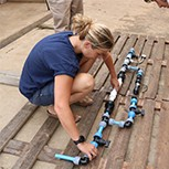 Francesca is on the floor assembling the chlorine test rig while in Uganda. Someone stands over her, ready to assist.